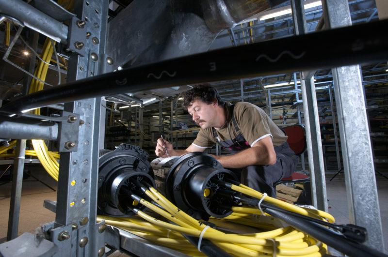 Industriefotografie: Ein Techniker verbindet in einer Vermittlungsstelle Glasfaserkabel.