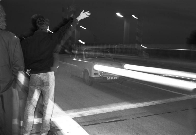 Reportagefotografie DDR Grenzöffnung 1989: Fahrzeuge aus der DDR fahren über die offene Grenze am Grenzübergang Helmstedt/Marienborn und werden von winkenden Westdeutschen begrüßt.