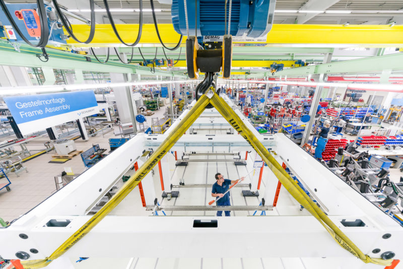 Industrial photography: An employee of a manufacturer of packaging systems works on the base frame of a machine. On the wide-angle photo you can see more workplaces in the large assembly hall.