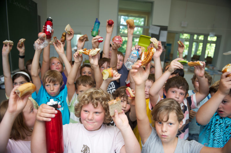 Editorial photography: Children of a primary school class hold the food to the camera they have brought with them, which they eat together during their break. They may drink at any time during the lesson.