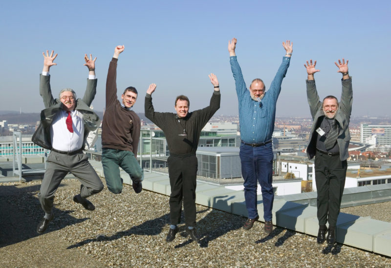 Group shot: 5 employees jump at the same time into the air on the roof of their company building. Their company IDs are flying around.