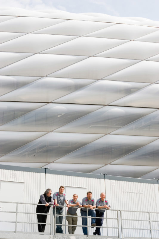 Group shot: Four employees of a telecommunications company are standing on the edge of the roof of the FC Bayern Munich stadium, where they are in charge of the mobile phone facilities.
