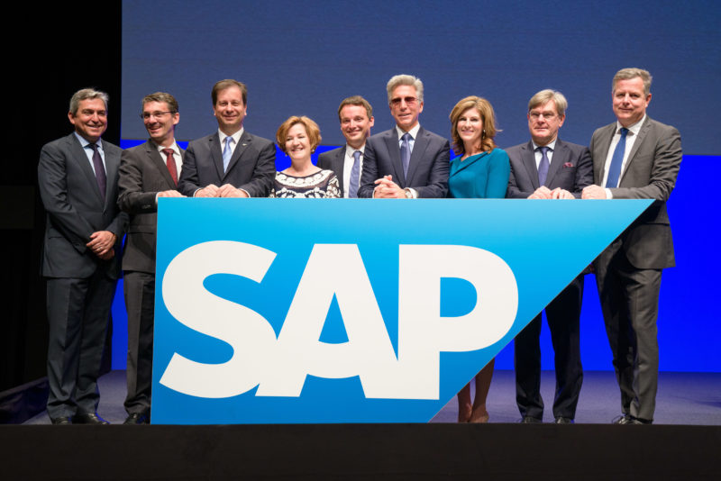 Group photo: Group picture of the management of SAP SE at the beginning of the Annual General Meeting. Everyone is standing on stage behind a large SAP logo.