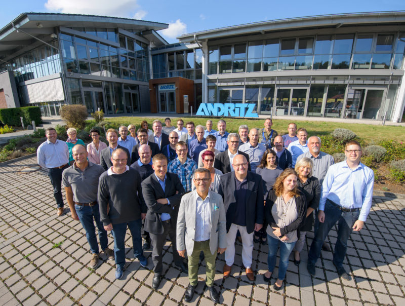 Group photo:  Staff in front of their company building. The boss stands in front, behind of all you can see the company building with large glass surfaces and the logo in front.