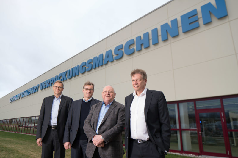 Group photo: The four managing directors of a medium-sized company outside in front of the company building on which the logo of the company is emblazoned.