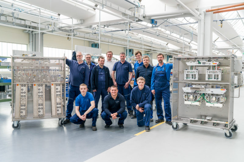 Group photo: Proud employees in the production of a company. They stand in the bright factory hall between rolling shelves with components. They all wear work clothes with the company logo sewn on them.