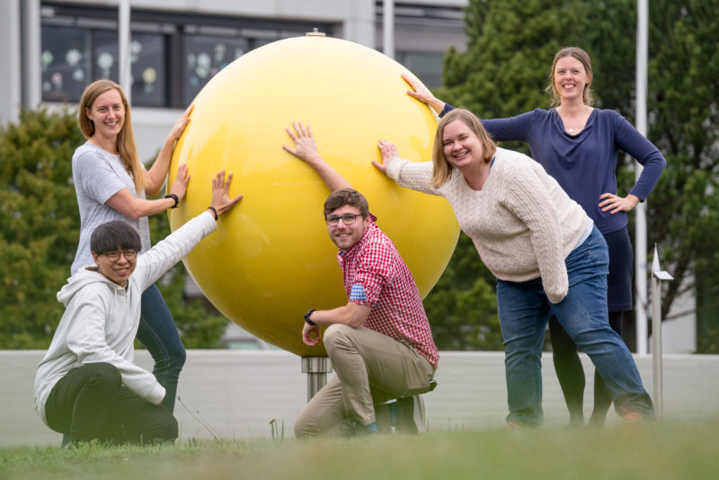 Group shot: Group photo: 5 employees of an astronomical research institute in front of the main building of the facility. They have their hands on a large yellow ball, a symbolic representation of the sun.