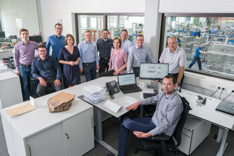 Group photo: Portrait of a group of 11 employees of a department. The picture was taken with a flash system, so that the people in the interior are still harmoniously illuminated and one can still look through the glass panes into the brightly lit production hall, in which another employee is moving a workpiece.