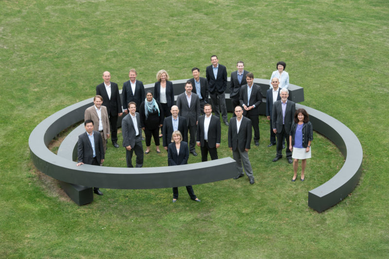 Group photos: Portrait of about 30 persons of a company department. The picture was taken with a long focal length from a nearby building. The people stand loosely grouped within a large, round artistic sculpture on the green lawn.