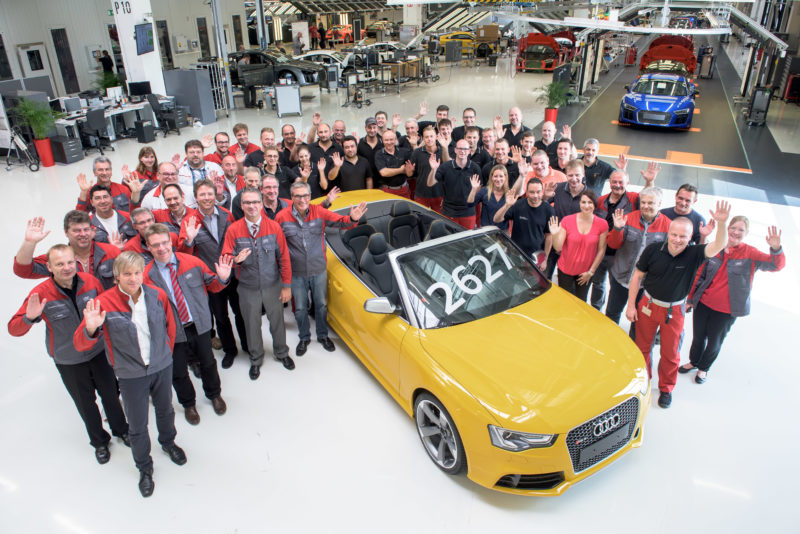 Group photo: The employees at the assembly line of an automibile production celebrate the construction of an anniversary vehicle. The car is in the middle and the colleagues wave into the camera, while you can see the production in the background.