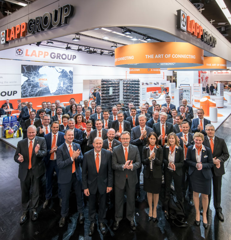 Group photo: Portrait of the entire stand personnel for the appearance of a company at an international trade fair. In the background you can see the entire exhibition stand.