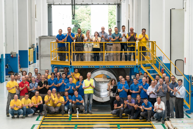 Group photo: Employees of a metalworking company in one of the factory buildings. Everyone wears goggles and claps.