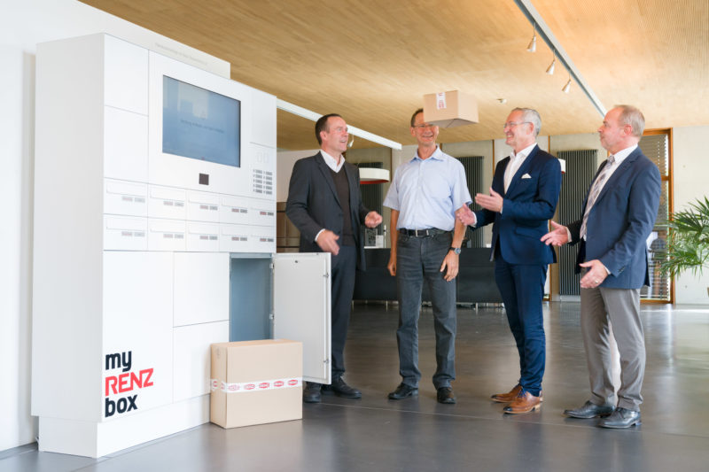 Group photo: Project members stand by their finished product, a mailbox-like, networked storage box for parcels. They