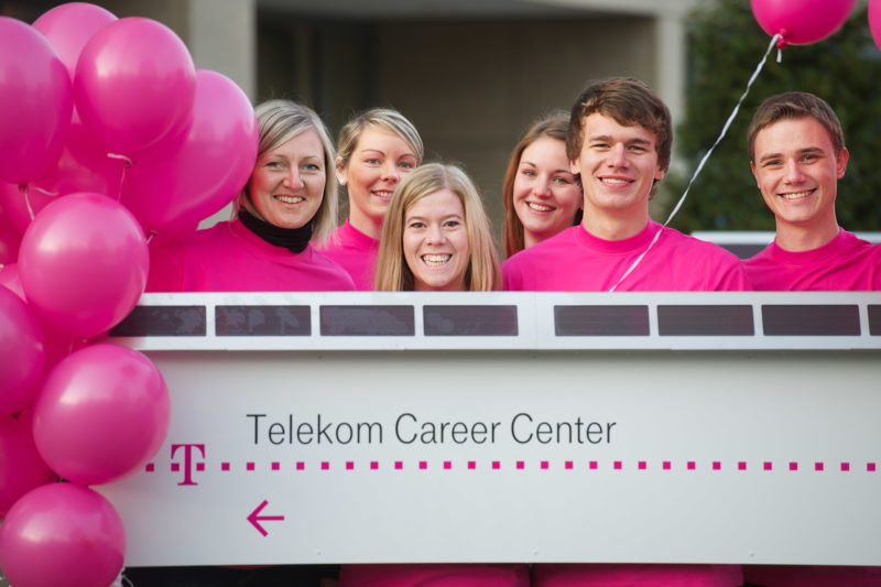 Group photo: A group of trainees is behind the label of the Telekom Career Center in Bonn.