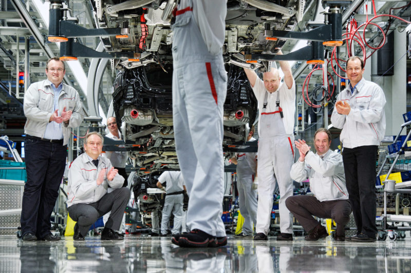 Group photo: A group of engineers on the production line in the vehicle manufacturing.