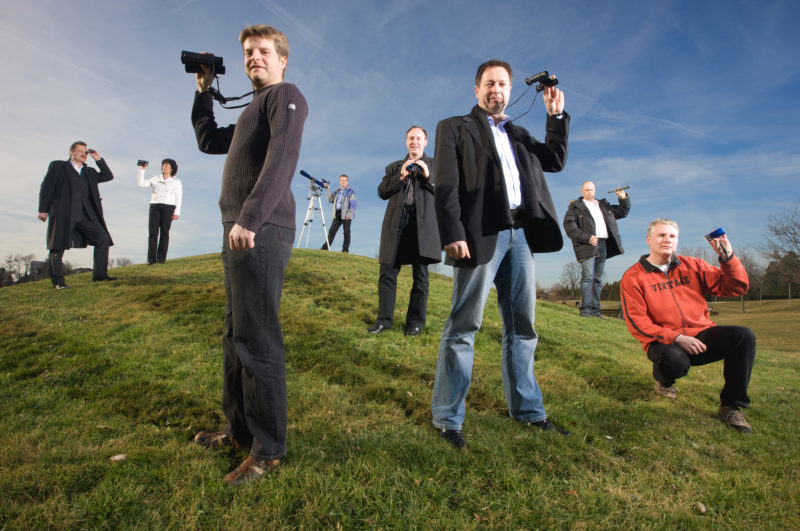 Group shot: Employees Portrait: Group photo of employees of a department for Trend Research. They stand on a hill and look through binoculars.
