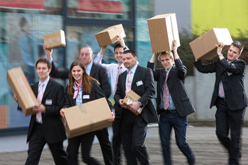 Group photo: The employees of a telecom stores carry boxes of goods to their store.