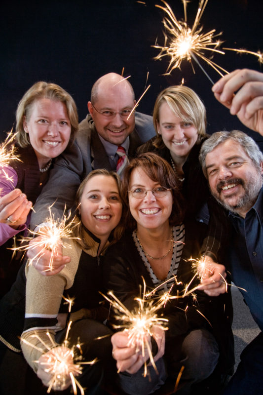 Group shot: Group picture: Employees with sparklers modeling for a poster for the New Years Eve party.