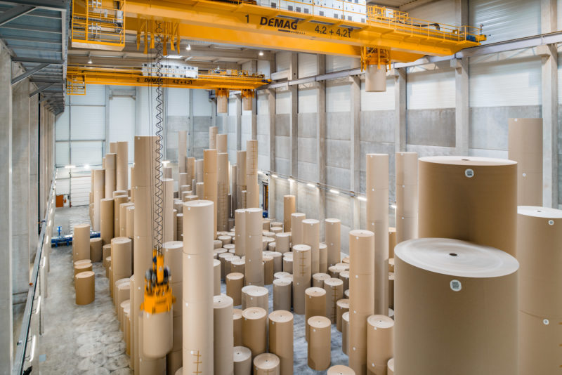 Industrial photography: Two indoor overhead traveling cranes move vertically stacked rolls of brown cardboard paper weighing several tons in a paper warehouse of a paper mill near Strasbourg.