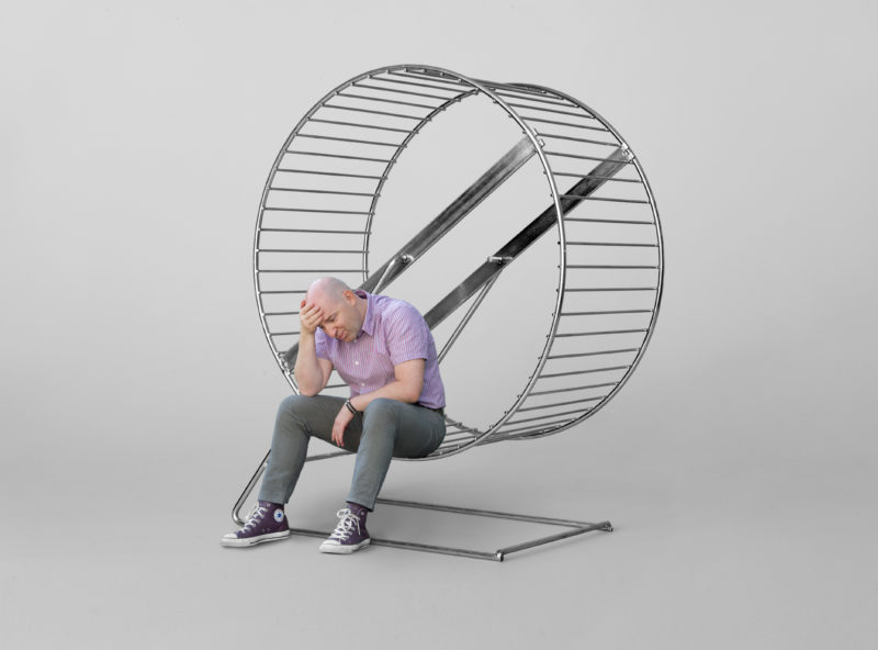 Photomontage with Photoshop: A man sitting exhausted in the rat race.