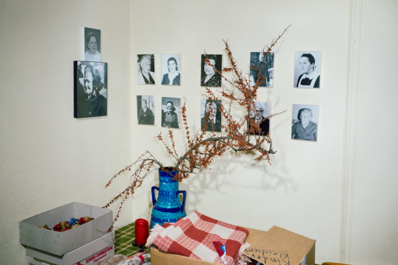Editorial photography at the Salvation Army: On the wall of a room at the Salvation Army hang photos of former female officers. On the table are Christmas decorations in cardboard boxes.