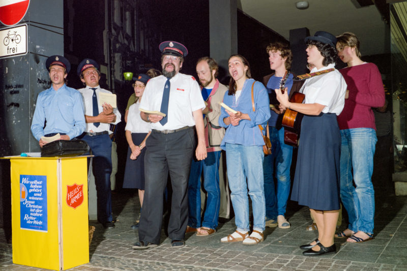 Editorial photography at the Salvation Army: The Salvation Army lives largely from donations. They sing Christian songs with guitars and in choirs, preferably in the evenings in lively pubs and in busy squares to raise money.