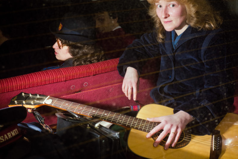 Editorial photography at the Salvation Army: A member of the Salvation Army sits with a guitar in the trunk of a car that takes her to the next venue where donations are collected.