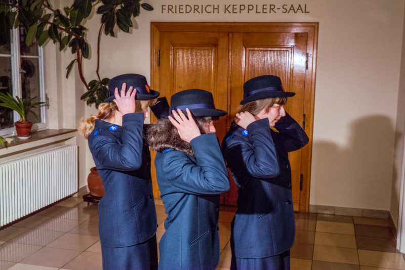 Editorial photography at the Salvation Army: Three young cadet girls put on the official officer