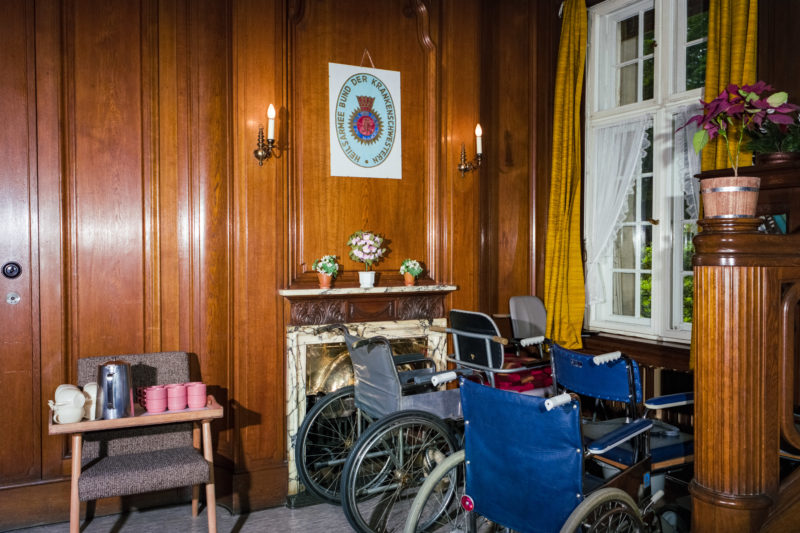 Editorial photography at the Salvation Army: In a Salvation Army nursing home, wheelchairs are placed in a wood-panelled, ornate room around an open fireplace.