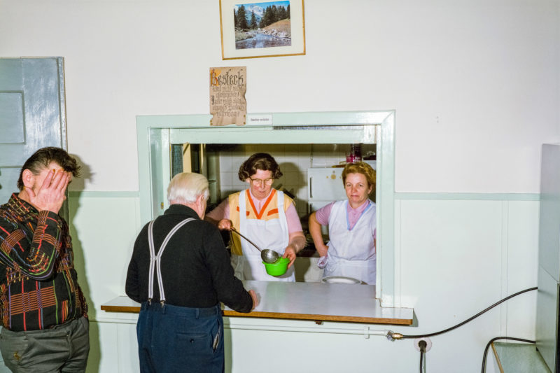Editorial photography at the Salvation Army: Two women in white aprons serve soup to the needy. Above the window to the kitchen hangs a picture of a beautiful alpine landscape.
