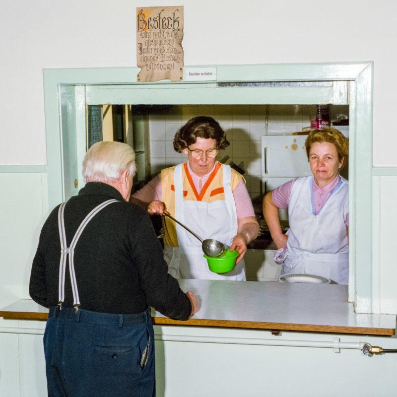 Luftaufnahmen und Drohnenfotografie: Reportagefotografie bei der Heilsarmee: Zwei Frauen in weißen Schürzen schenken Suppe an Bedürftige aus. Über dem Fenster zur Küche hängt ein Bild einer schönen Alpenlandschaft.