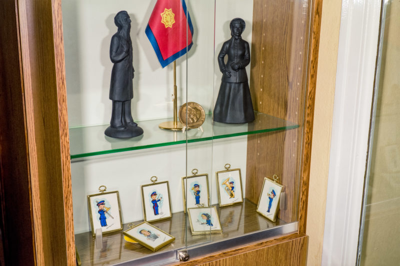 Editorial photography at the Salvation Army: A display case in a Salvation Army facility. Orders and flags stand next to kitschy pictures of Salvation Army musicians and stone figures.