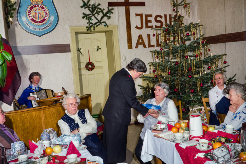 Editorial photography at the Salvation Army: At a Christmas party in a Salvation Army retirement home, the residents receive gifts and coffee and cake. A decorated tree and a cross decorate the room.