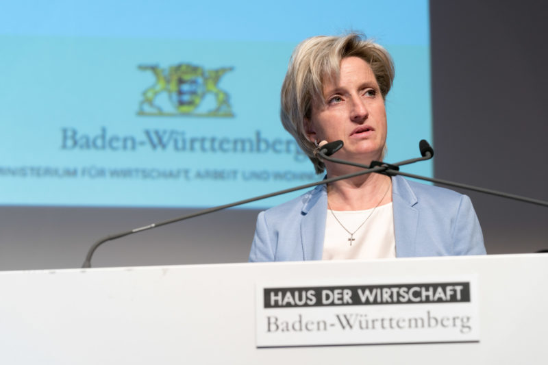Event photography, editorial photography: Dr. Nicole Hoffmeister-Kraut, Minister of Economic Affairs, Labour and Housing of the State of Baden-Württemberg, gives a speech during an event at the Haus der Wirtschaft in Stuttgart. In the foreground you can see the logo of the house and in the background the logo of the state of Baden-Württemberg.