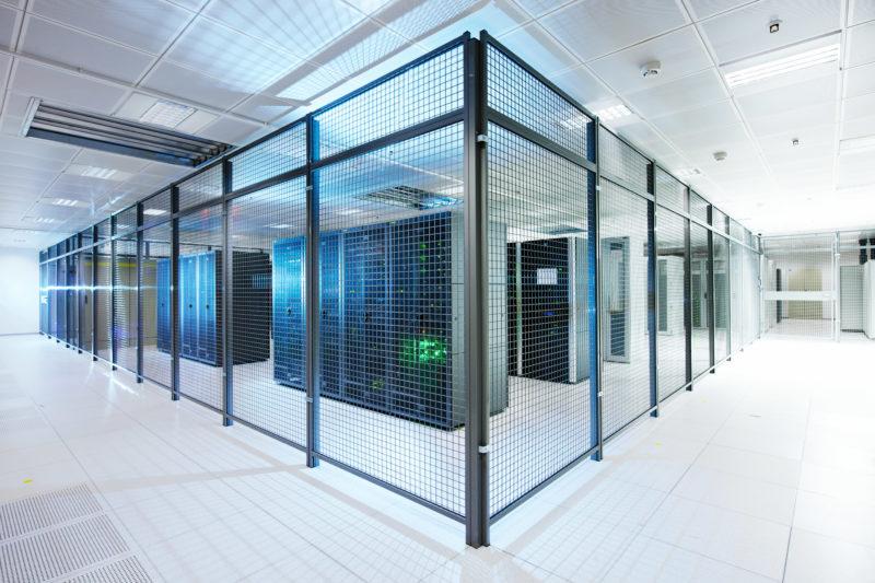 Industriefotografie: In mit Gitter getrennten Abteilen stehen die Hosted Server in einem Rechenzentrums.