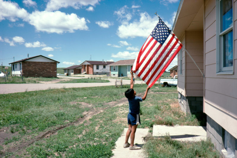 Reportage photography on slide film in the Pine Ridge Reservation in South Dakota, USA: A boy smoothes an American flag hanging from his family