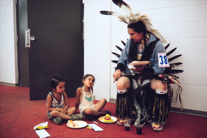 Reportage photography on slide film in the Pine Ridge Reservation in South Dakota, USA: During a dance competition a dancer in full ornament sits with his children in the corridor to eat from paper plates.