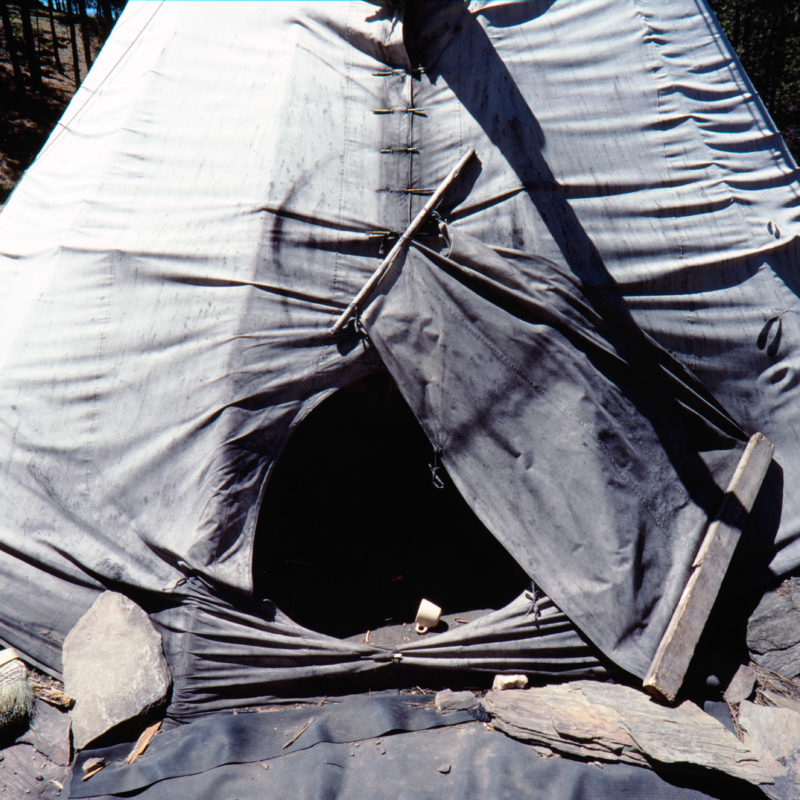 Luftaufnahmen und Drohnenfotografie: Reportagefotografie auf Diafilm in der Pine Ridge Reservation in South Dakota, USA: Ein verlassenes Indianerzelt in einem Wald, in dem sich Mitglieder des American Indian Movement treffen.