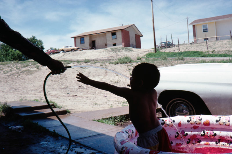 Reportage photography on slide film in the Pine Ridge Reservation in South Dakota, USA: A child plays with water from a hose while sitting for washing in a plastic paddling pool in a settlement.
