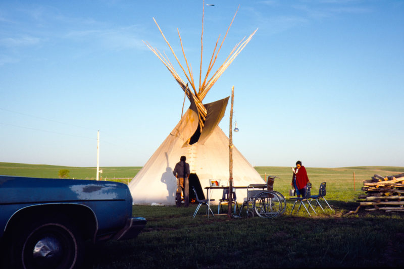 Reportage photography on slide film in the Pine Ridge Reservation in South Dakota, USA: A woman with an eagle feather in her hand carries water into the tent, where a sweating ceremony is just beginning.