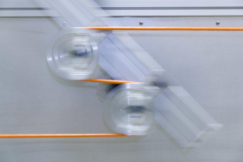 Industriefotografie: In einem Prüflabor: Die mechanische Belastungsfähigkeit eines Kabels wird durch einen Dauerbewegungstest untersucht.