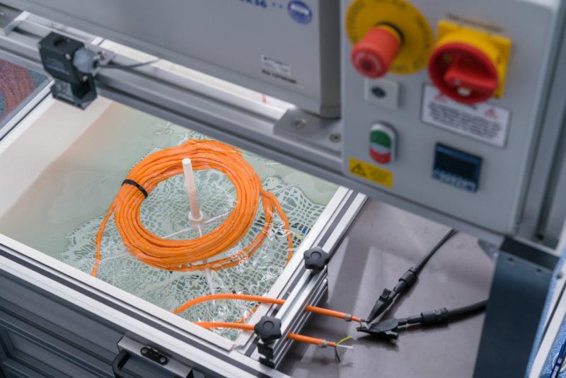 Industriefotografie: In einem Prüflabor: Die Isolation eines Kabels wird auf ihre Wasserfestigkeit geprüft.
