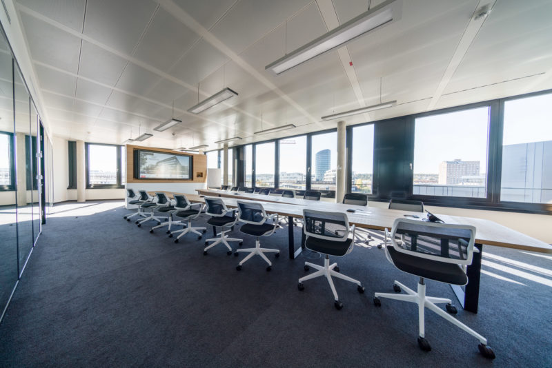 Architectural photography: Interior view of a modern, new conference room in an office building. The open architecture with the view from the glass facade elements illuminates the room with the large table and many chairs in a natural way.