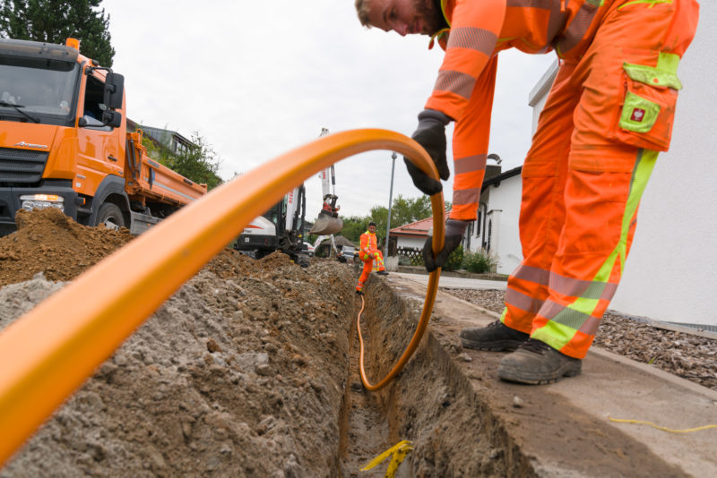 Industrial photography:  For the Internet broadband expansion in rural regions, fiber optic cables are laid under a sidewalk in a housing estate. Two workers lower a laying pipe into the trench through which the fiber optic cables are later blown.