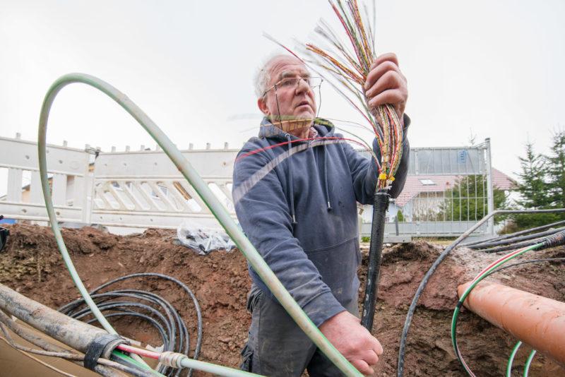 Industriefotografie: Internetausbau auf der Straße: Ein Techniker steht im ausgehobenen Graben und hat ein Kabelbündel mit Telefon und Datenleitungen in der Hand, um dieses an einem neuen Verteiler mit Glasfasereingang anzuschließen.