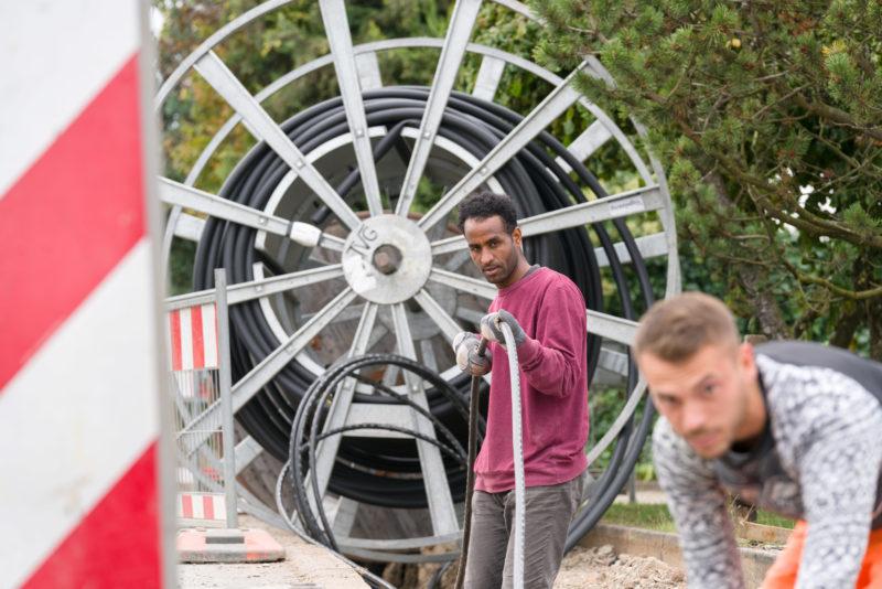 Industriefotografie: Auf einer Baustelle zur Erweiterung der Internetversorgung verlegen zwei Arbeiter ein neues Kabel. Im Hintergrund sieht man die große Trommel mit der schwarzen Erdleitung.