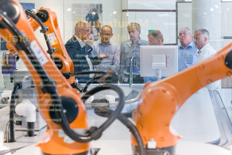 Technology photography:  Visitors of a guided tour of the Internet of Things iOT demonstration plant at SAP SE in Walldorf, where networked production technology is demonstrated.