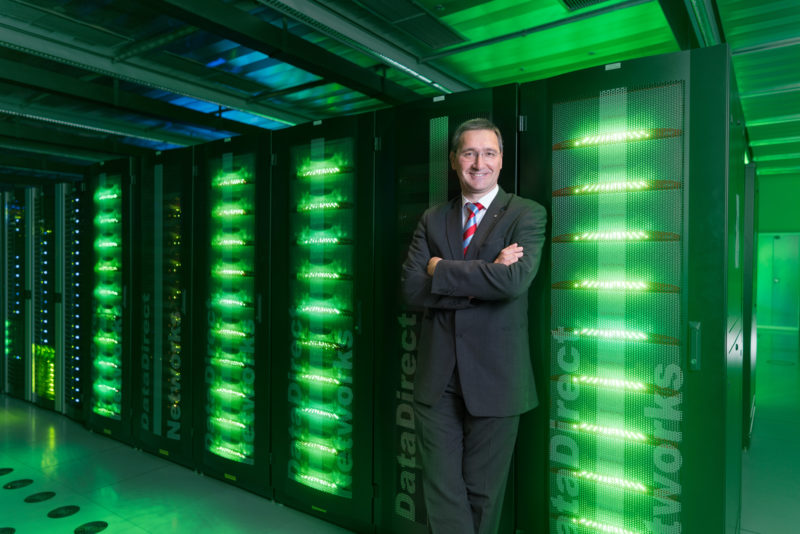 Managerportrait: A head of an IT department is leaning against one of the many green glowing black servers in his data center.