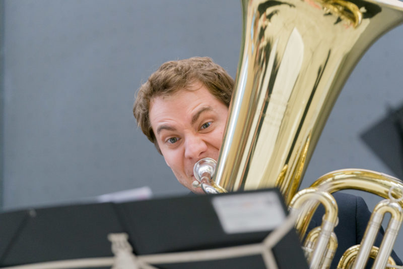 Editorial photography as event photography and fair photography: At an anniversary event of a university, a member of the university orchestra plays with inflated cheeks on the tuba.