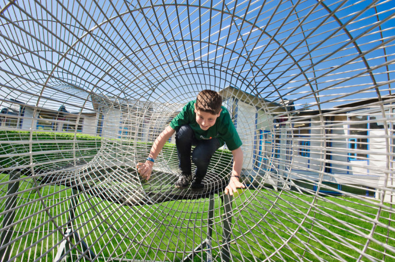 Editorial photography: A boy crawls enthusiastically through a tube made of iron wire, which is shaped in such a way that a geometric law can be explained with it. Above him the blue sky. Green grass under him.